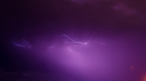 Lightning in Purple Sky during Night Time