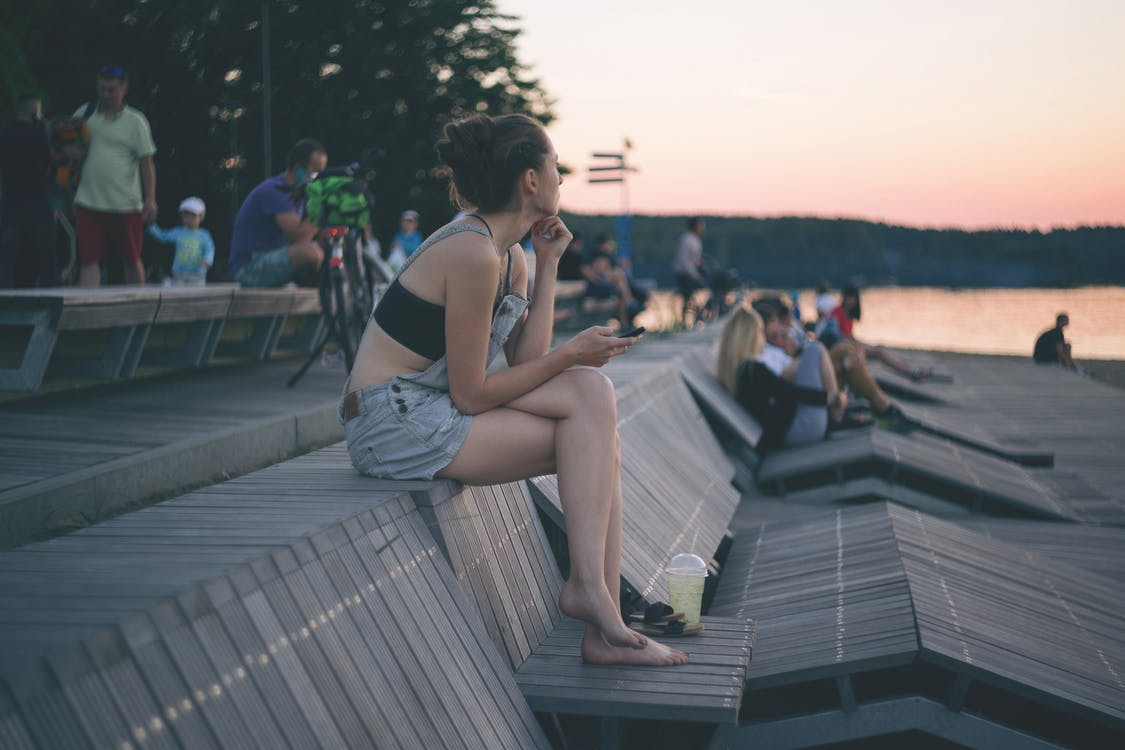 Woman Crossing Her Legs While Sitting Near Bay