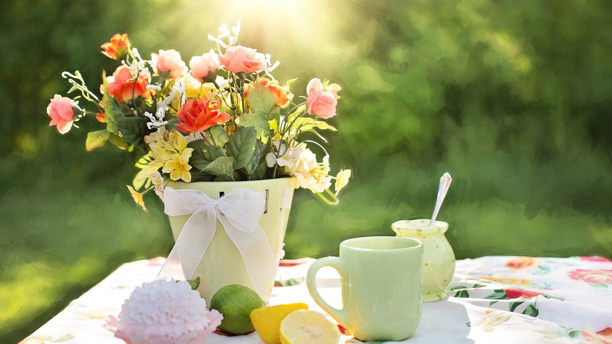 Assorted Flowers on Container Beside Mug on Table