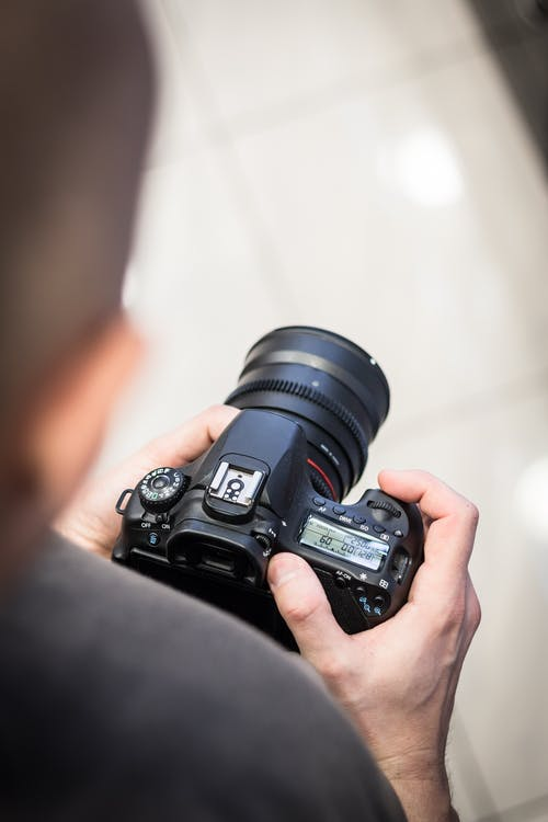 Person Holding Dslr Camera in Shallow Photo