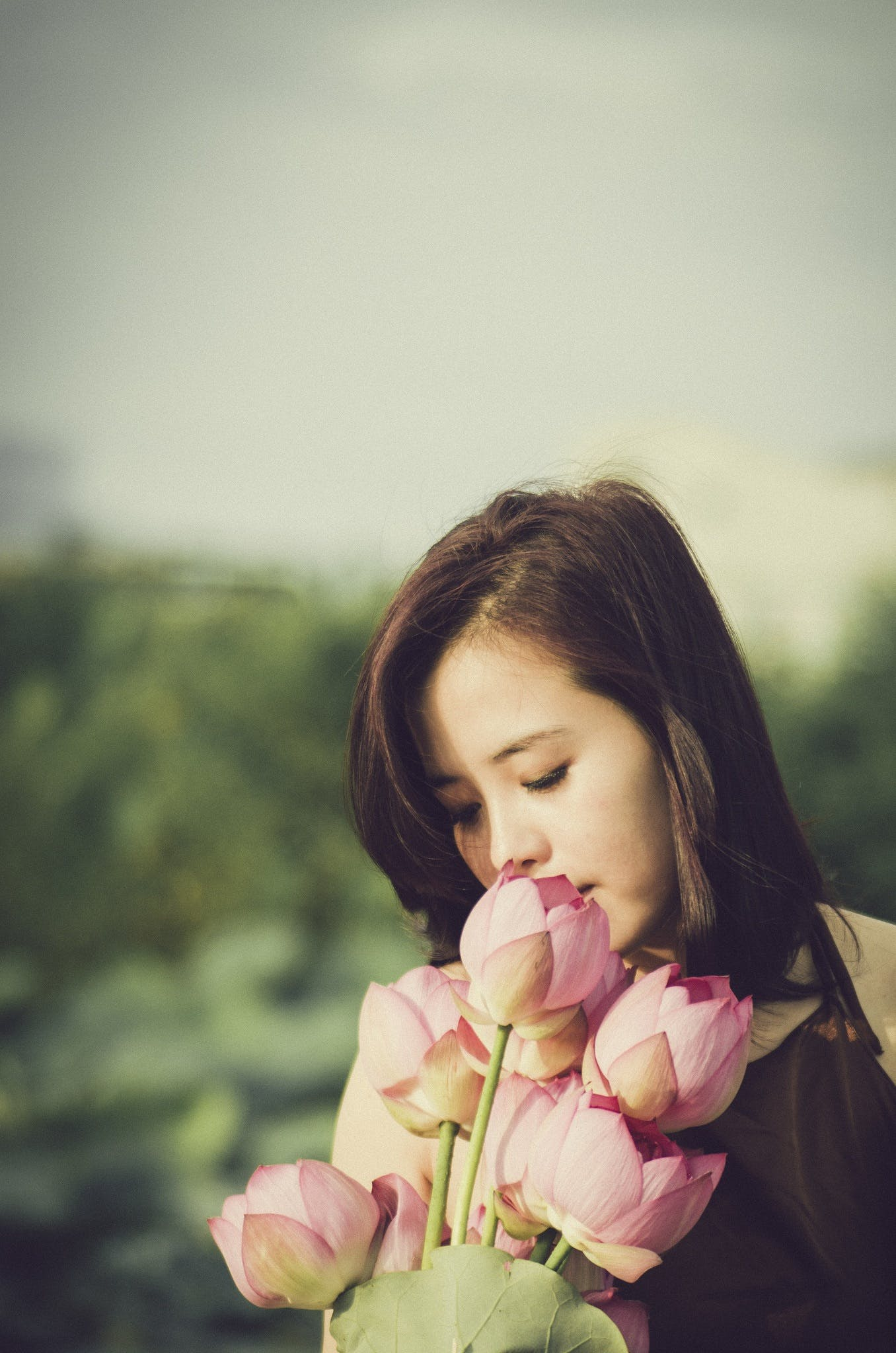 Woman in Brown and White Sniffing Pink Flowering Plant