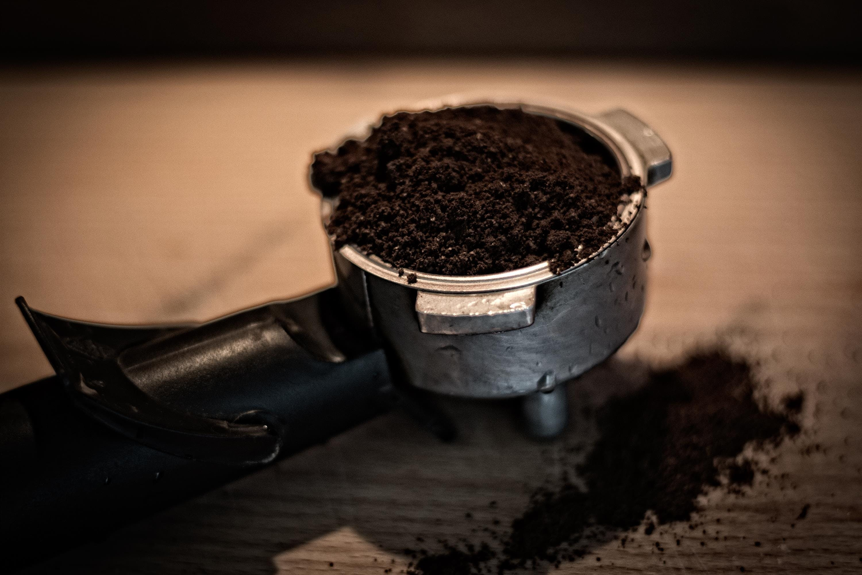 Grey and Black Coffee Cup Filled With Grind Coffee