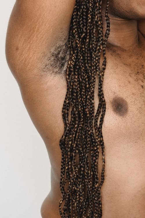 Crop shirtless plump black man with raised arms