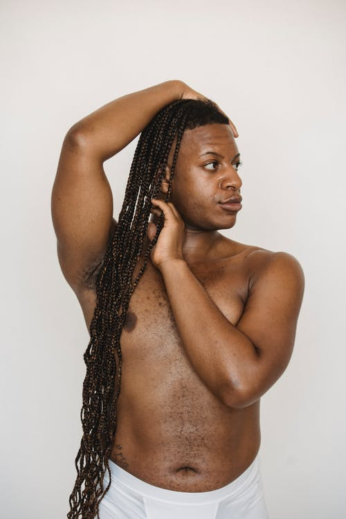 Androgynous shirtless black man with hand on head