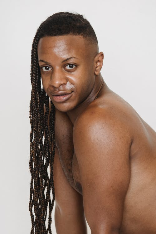 Content African American male with Afro braids and naked torso looking at camera while leaning forward on white background in studio