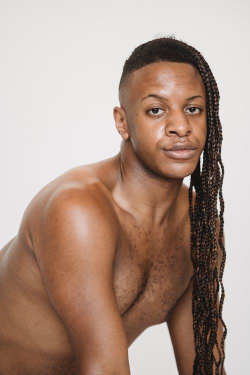Feminine shirtless black man with Afro braids