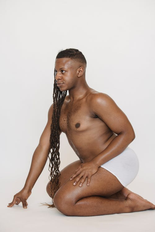 Side view of feminine African American male in underpants with Afro braids sitting on knees and leaning forward on white background