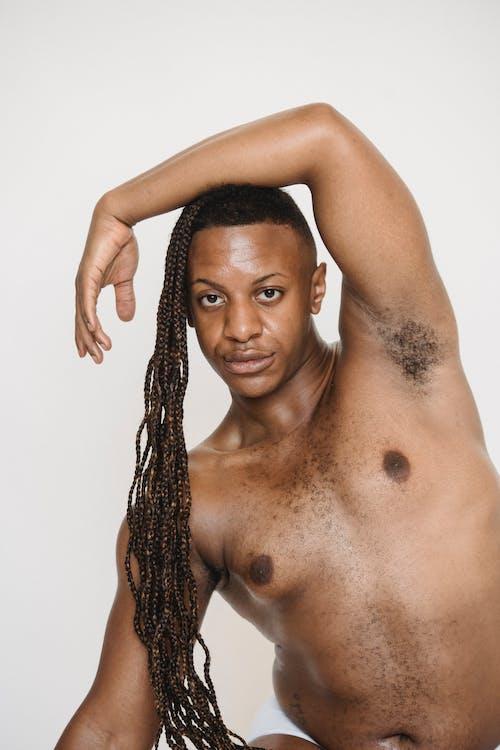 Feminine shirtless black man in studio