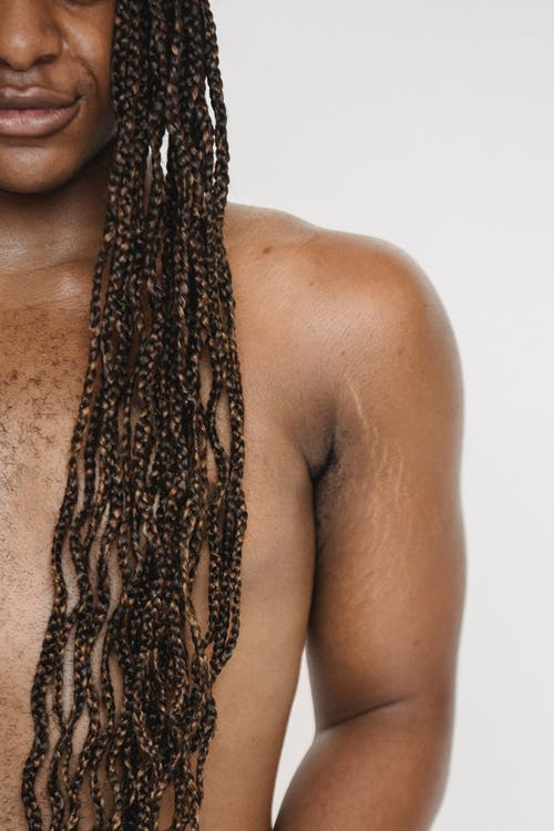 Unrecognizable queer androgynous African American male with naked torso and long Afro braids standing on white background in modern studio