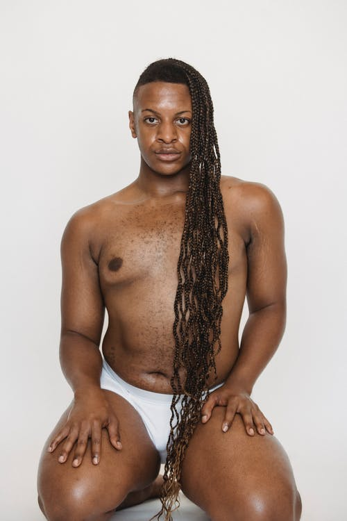 Confident feminine African American male wearing white underwear looking at camera while sitting on knees on white background with hands on thighs