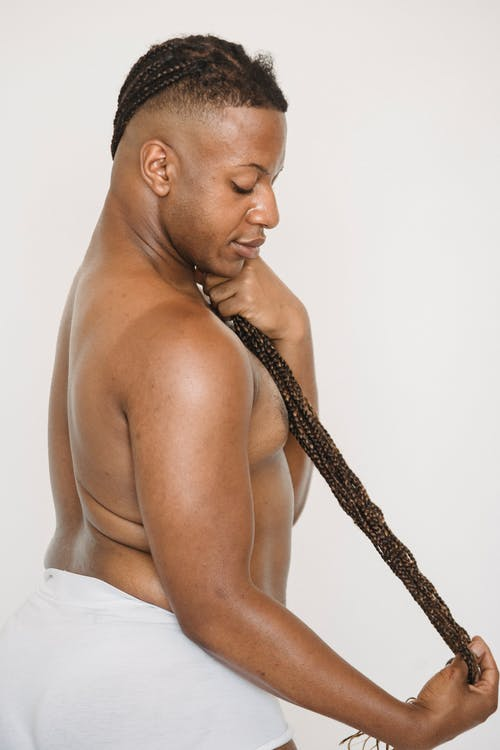 Side view of African American shirtless androgynous male touching long braided hairstyle and looking down on white background