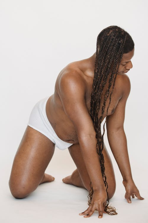 Black feminine man with long braided hairstyle on all fours