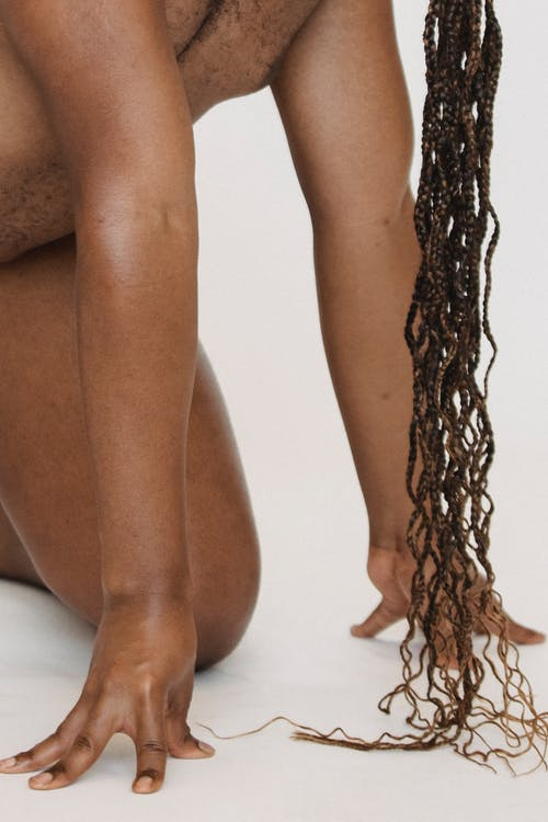 Homosexual crop anonymous African American male with braided hairstyle on all fours in studio on white background