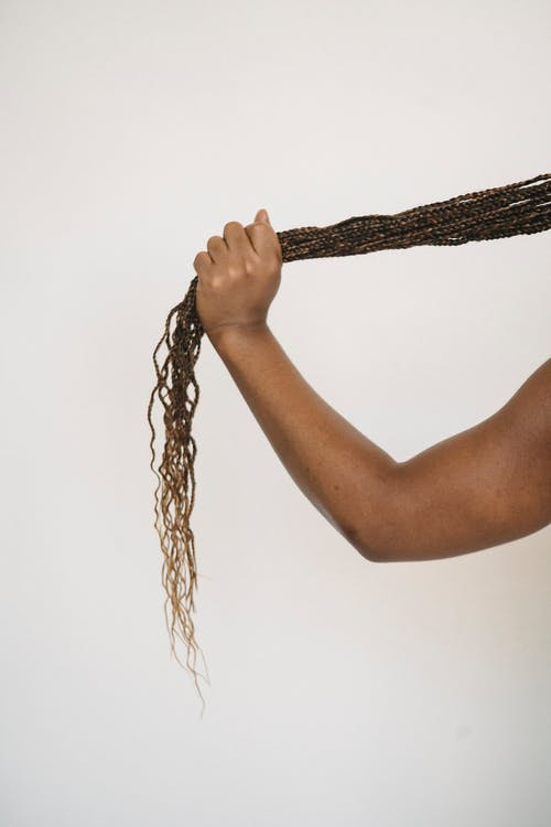 Crop faceless ethnic person touching ponytail of African braids