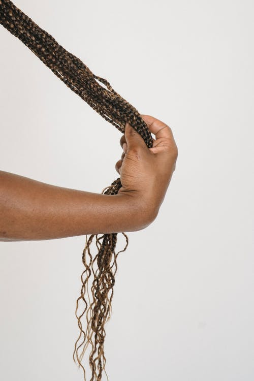 Crop unrecognizable ethnic person touching long ponytail of African braids against white wall in light studio
