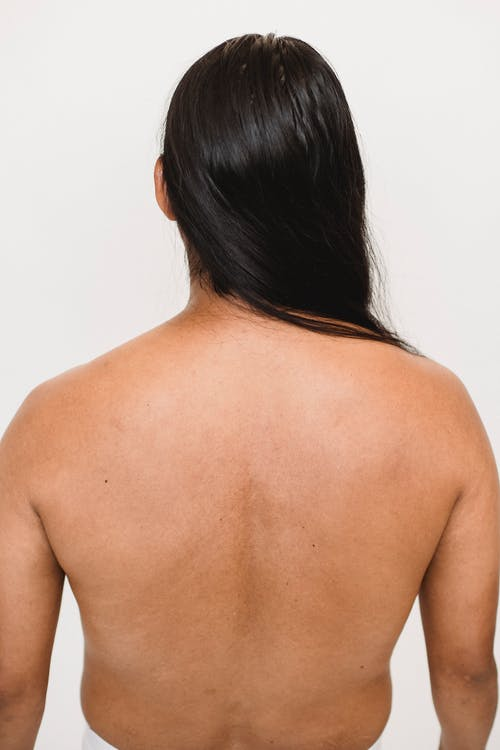 Faceless ethnic person with naked back and smooth hair