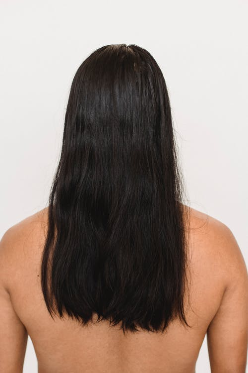 Back view of anonymous ethnic person with naked torso and black hair on white background