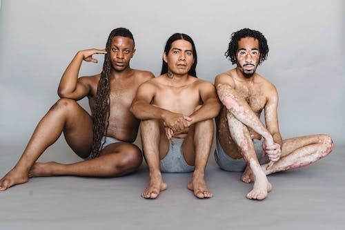 Unemotional diverse men in underpants sitting on floor