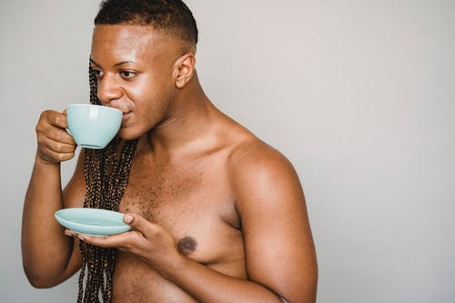 Crop African American male with naked torso and long braids standing against gray wall and enjoying hot drink from ceramic cup