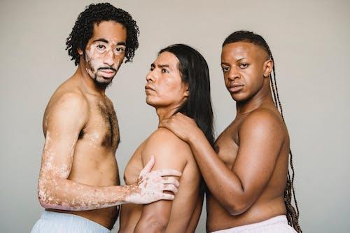 Multiethnic homosexual calm men with naked torso standing in studio