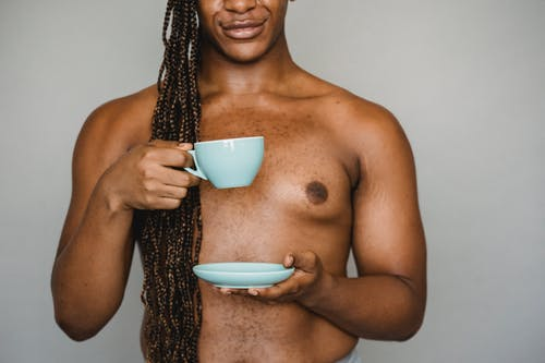 Crop African American male with naked torso and long hair pouting lips while standing against gray wall with cup of hot drink