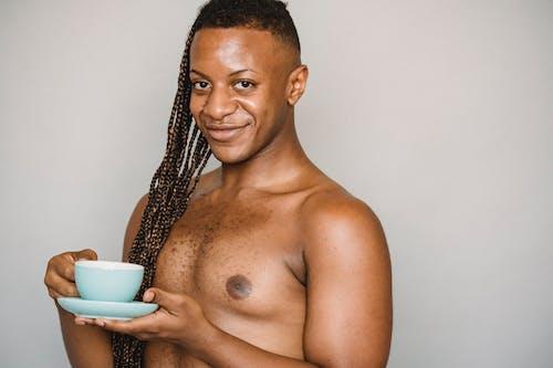 Crop shirtless black man holding coffee cup