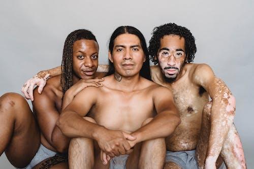 Positive Hemdlose Multiethnische Männer Sitzen Auf Dem Boden Und Umarmen Sich