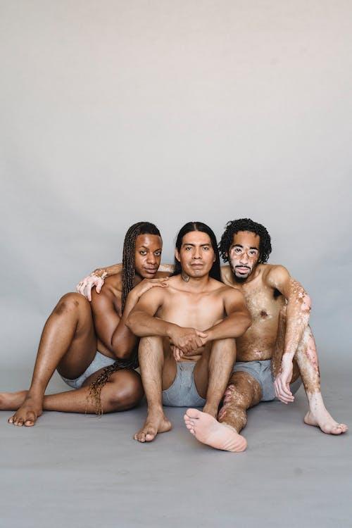 Zufriedene Multiethnische Hemdlose Männer, Die Auf Dem Boden Sitzen Und Sich Umarmen