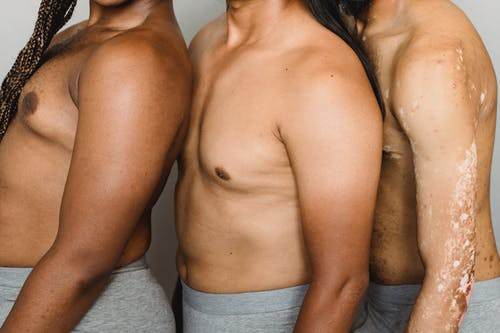 SIde view of crop anonymous multiracial homosexual men in underwear on white background of studio