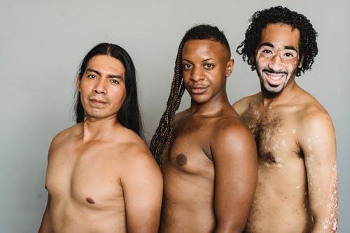 Happy multiracial group of friends with naked torso looking at camera and smiling on white background of studio