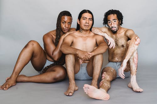 Full body multiracial men with naked torso looking at camera and sitting on white background of studio