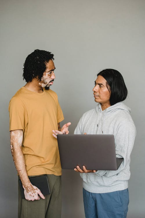 African American male with vitiligo skin talking to ethnic colleague surfing Internet during work together