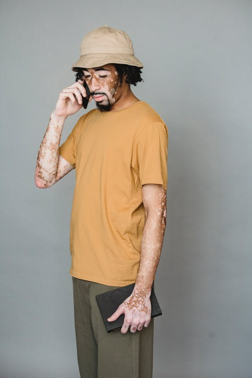 Bearded African American male with vitiligo body having conversation on mobile phone while standing with notebook against gray background