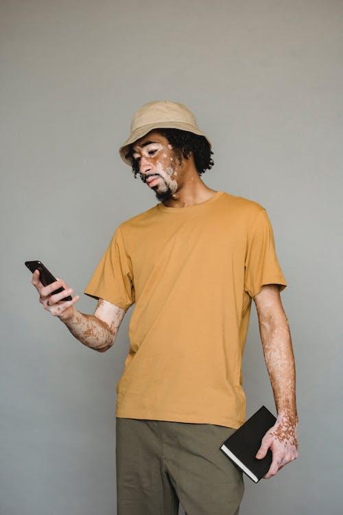 Serious black man browsing smartphone in studio