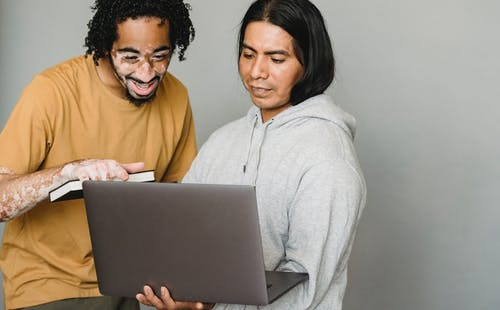 Positive multiracial coworkers discussing work together with laptop