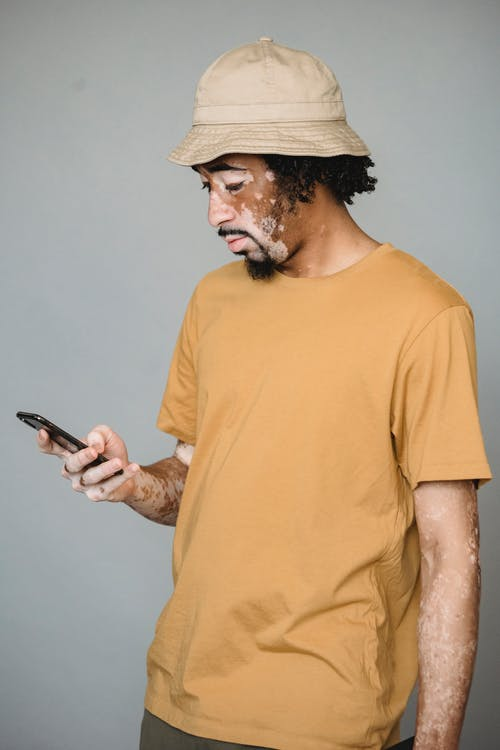 Focused black male with pigmented skin using smartphone