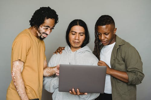 Multicultural coworkers surfing laptop while searching information together for work issues in studio against gray background
