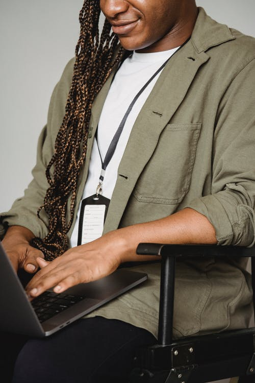 Positive crop African American male freelancer typing text on laptop while sitting in chair and working alone