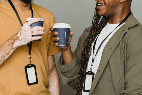 Smiling black man with braids having coffee with friend