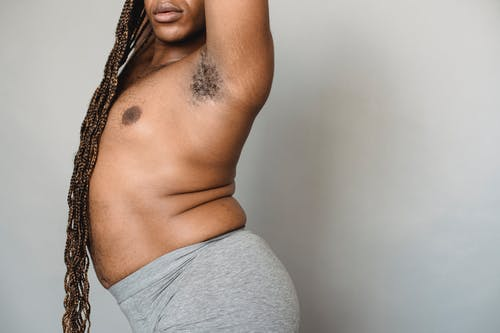 Unrecognizable plump androgynous African American male with Afro braids and naked torso standing on white background with raised arms and hairy armpit
