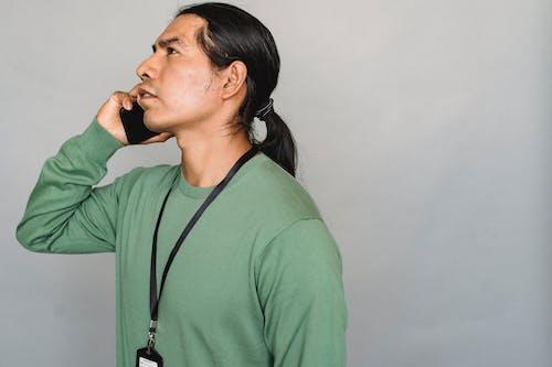 Serious Native American man having conversation on smartphone