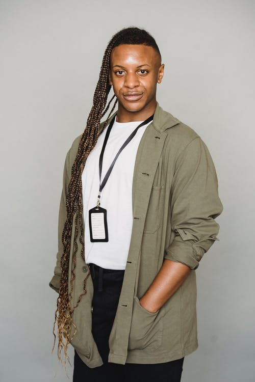 Androgynous African American male with Afro braids wearing id card looking at camera while standing on white background with hand in pocket