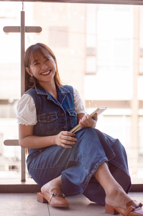 Joyful Asian woman with notebook in hands
