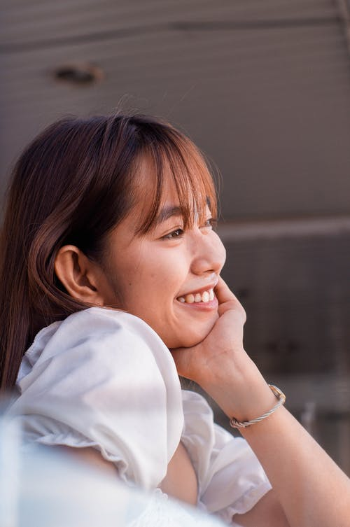 Side view of dreamy Asian female in white apparel leaning on hand and looking into distance while standing near blurred railing