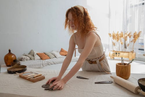 Craftswoman preparing clay equipment on table in light workspace