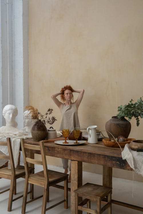 Young contemplative female carver touching hair and looking away near table with bust and potted plants
