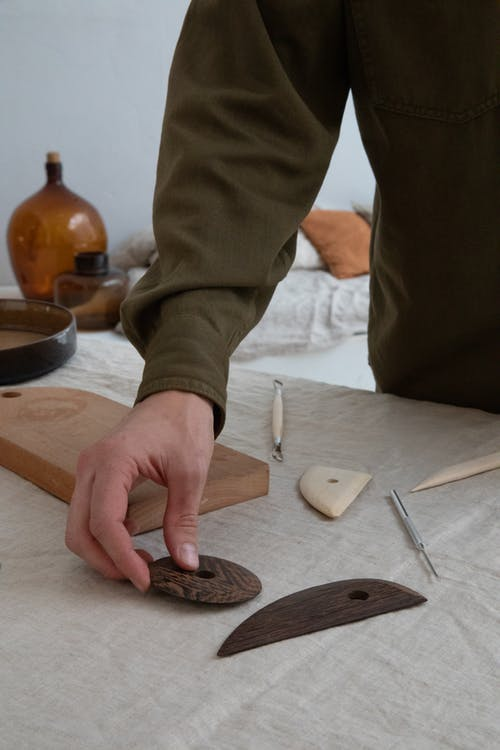 Faceless craftsman with clay equipment in workshop