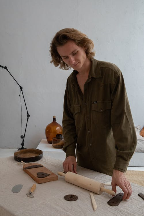 Young male artisan in casual apparel standing at table with different manual sculpting tools