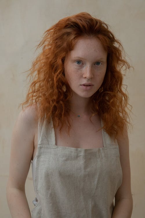 Gentle woman with red head and freckles on skin