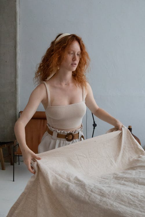 Young gentle female with red hair and fabric in casual apparel at home in daylight